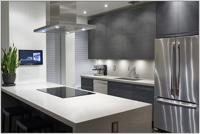 This Kitchen Has Two Hues Of Grey And White Blended Together. The Cabinets  Are In Grey Colour Under Which The White Led Lighting Is Doing Its Magic.